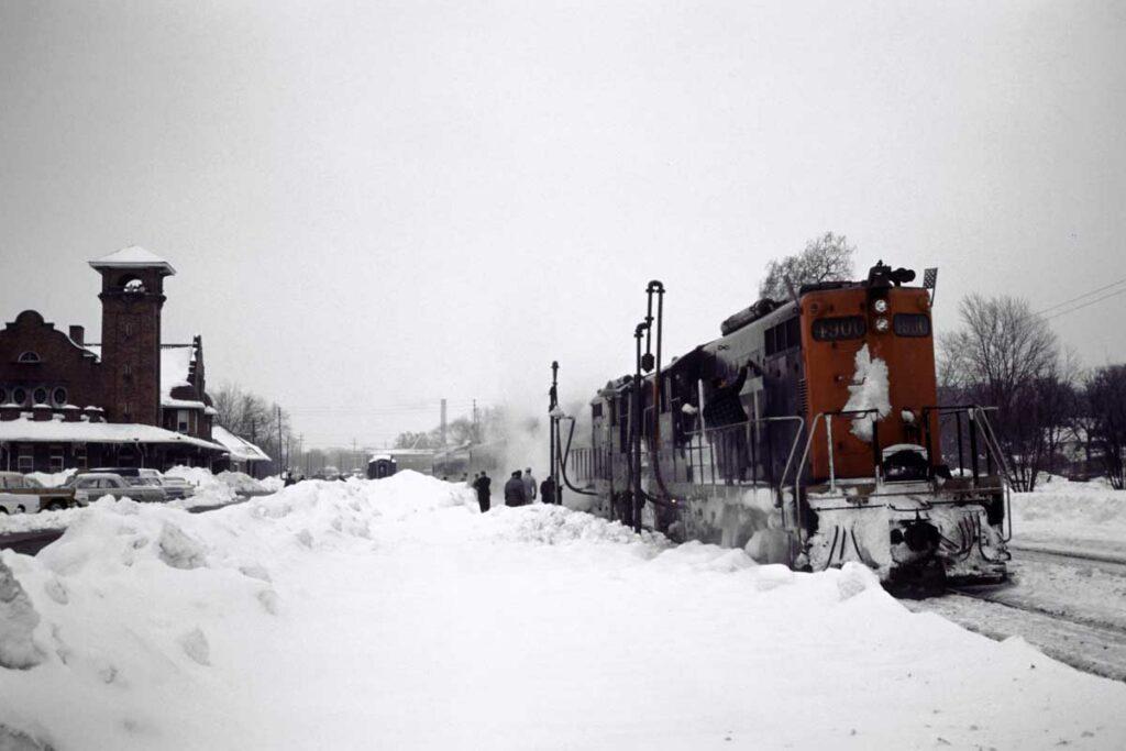 Diesel locomotives with passenger train at brick station in snow