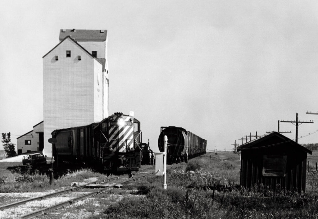 Diesel powered freight train switches cars at wooden grain elevator