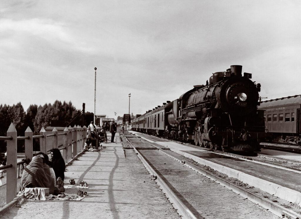 Steam locomotive with passenger train by station platform