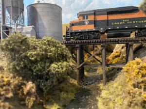 A model train passes over a bridge