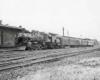 Steam locomotive with short passenger train at station