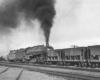 Steam locomotive pushing on rear of freight train