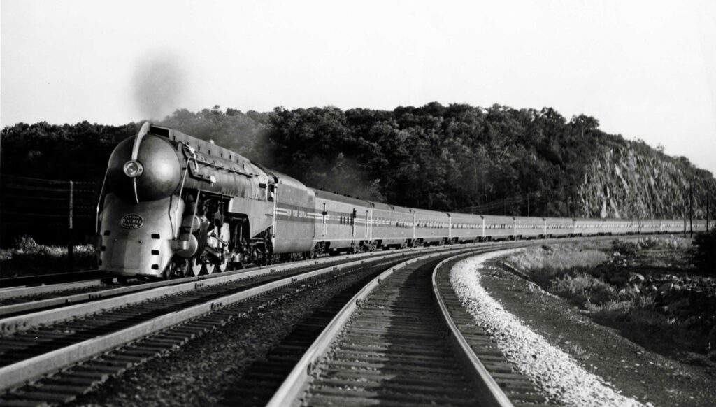 Streamlined steam locomotive leading a streamline passenger train on a gentle curve.