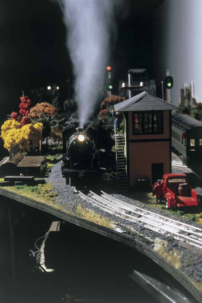 Front of an O gauge model steam locomotive on layout in night operation with smoke coming out of the stack next to interlocking tower.