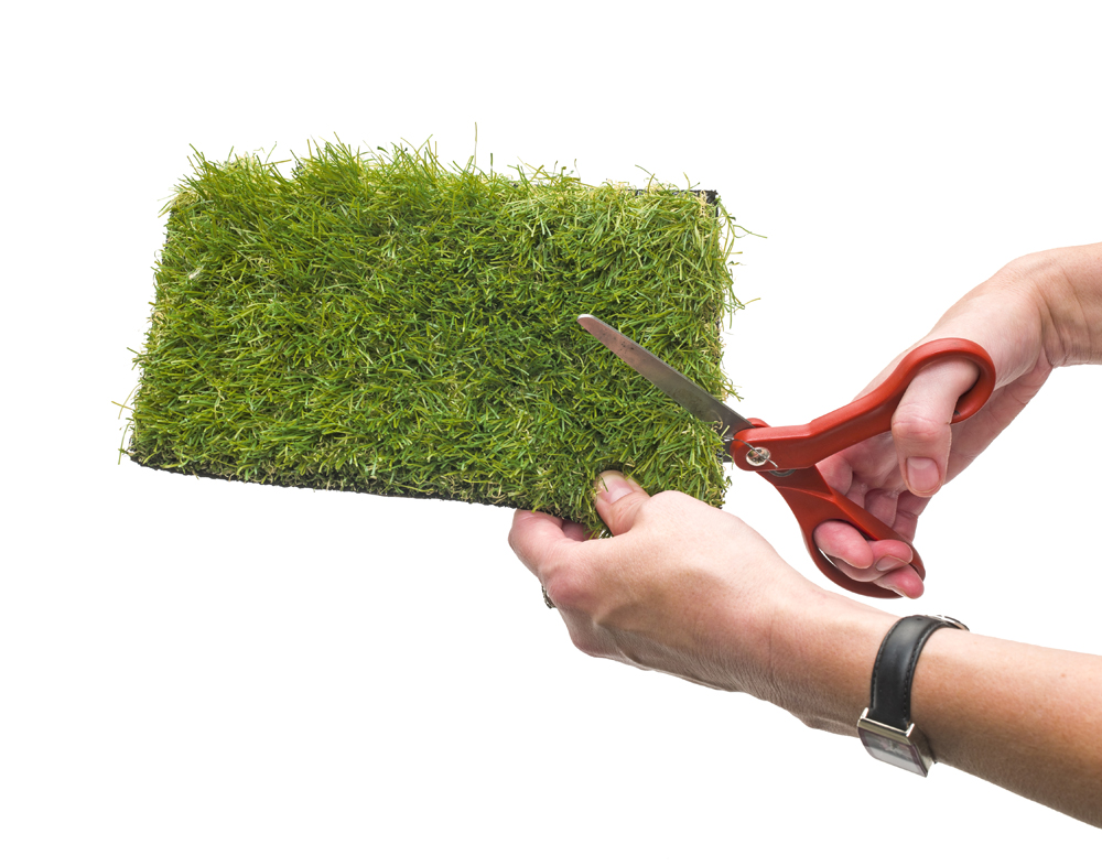 Scissors cutting a piece of outdoor carpet.