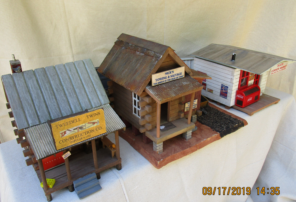 Three completed structures made from wooden birdhouses