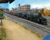 Union Pacific Big Boy moving left to right prepares to leave yard with mixed freight train, dirt rpad in foreground, industrial buildings in background
