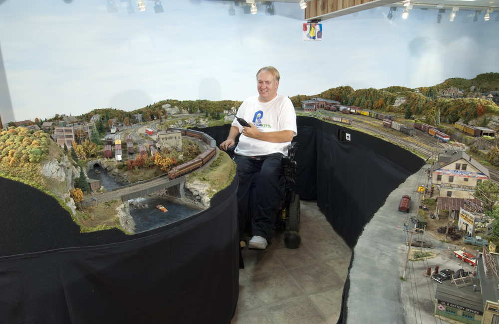 A man sitting in a wheelchair operates his HO scale model railroad