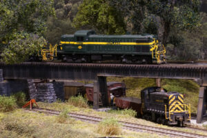A green road diesel leads a train over a steel girder bridge above a black diesel switcher with its own train