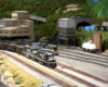 A pair of black diesels lead a loaded coal train while a diesel switcher works a mine in the background