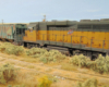 : A rusty yellow-and-green diesel and a worn green covered hopper roll down an equally neglected spur track on the prairie