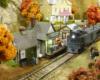 "A green ""Doodlebug"" motorcar pulls up to the platform at a small, yellow, wood-frame depot"