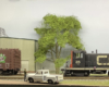 A black-and-red Canadian National switcher backs toward a brown CN boxcar in front of a corrugated metal building