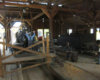 A steam locomotive being worked on is seen through the doorway of a wooden engine shop