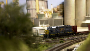 A CSX train sits in the middle of a track, the scene is partially covered by a bush