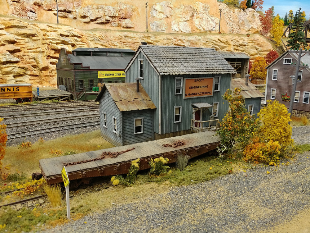 Gray board-and-batten two-story building with abandoned flatcar in foreground, main line running behind