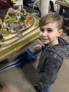 Gabriel Turlan stands in front of a model layout, running the trains