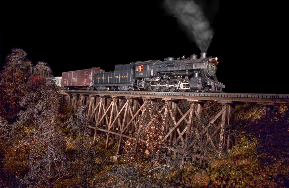A steam locomotive is dramatically lit from the side as it crosses a wood trestle at night