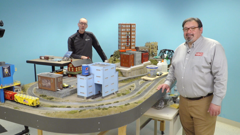 Two men standing on either side of a table-based toy train layout.