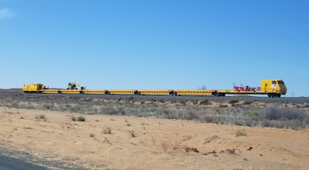 A yellow work train consisting of a squarish cab unit up front, a similar drive unit in back, and six gondolas in between, with a crane on top of the fifth gondola, is seen on a track in the desert