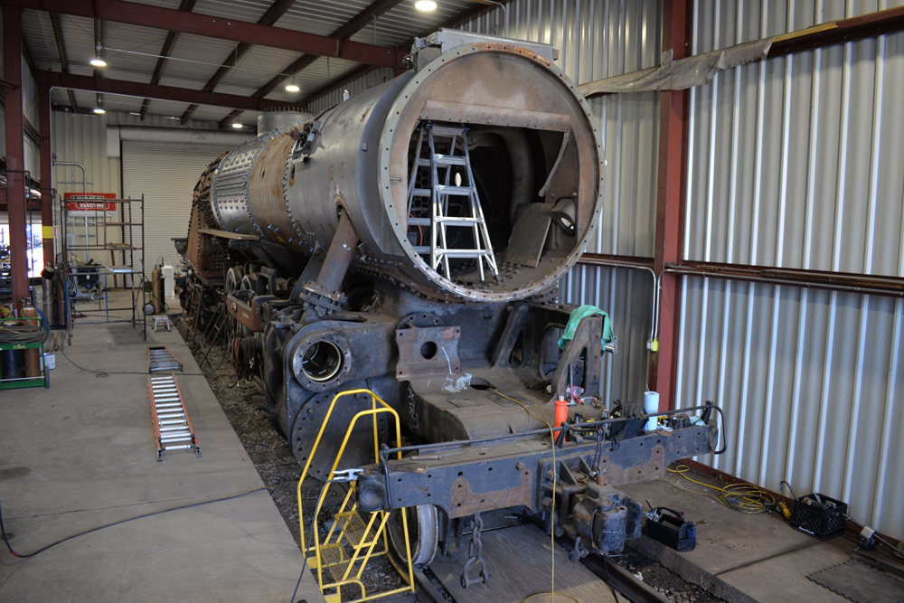 Steam engine being worked on in shop building