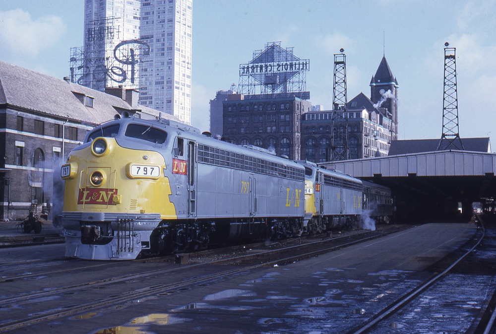 Gray and yellow locomotives on passenger train waiting to leave station