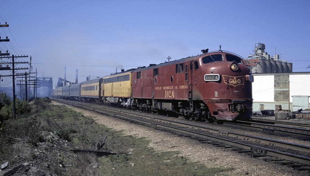Red and yellow locomotives leading passenger train with cars of several colors.
