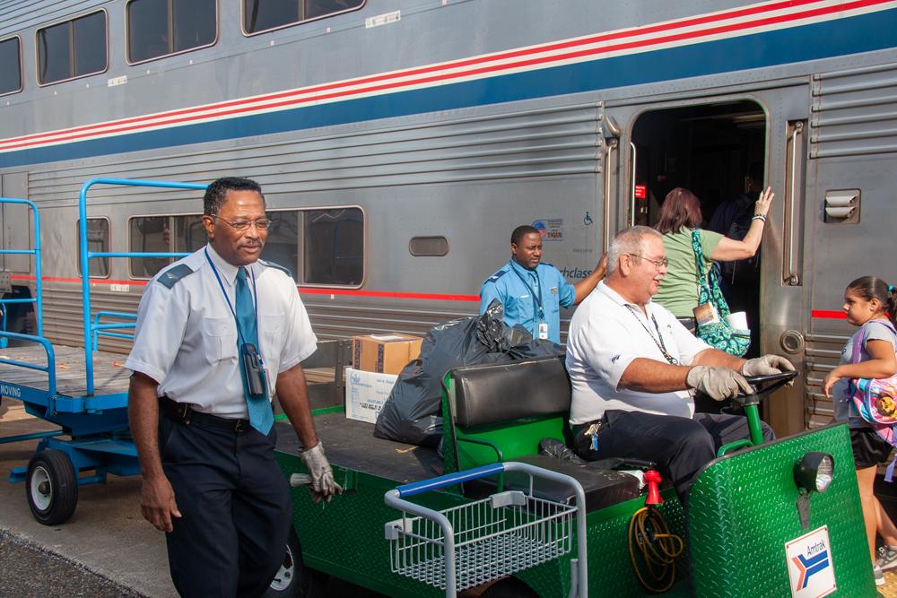Amtrak employee handling baggage next to train.
