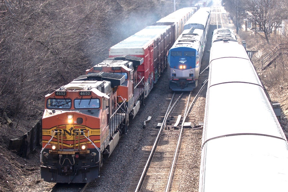 Three trains — one freight, two passengers — meet on triple-track main line.
