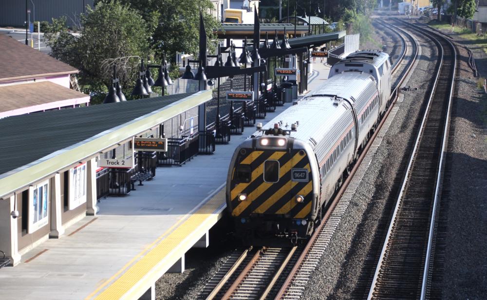 Cab car leads short passenger train past station