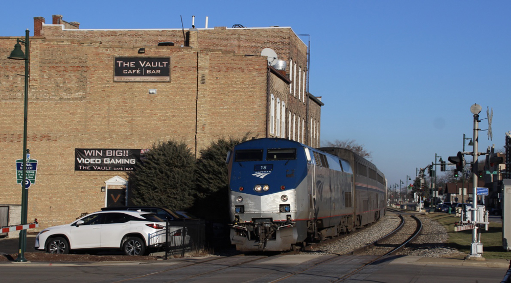 Train passes next to buildings in small town.