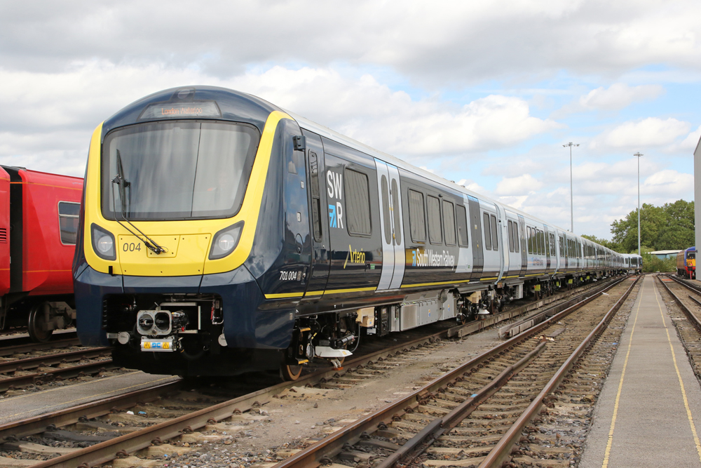 New blue and yellow passenger train sits in yard