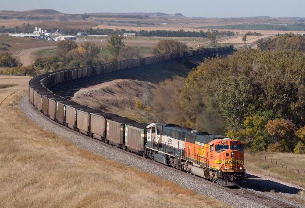 Diesel locomotives power a coal train around bend in rolling hills