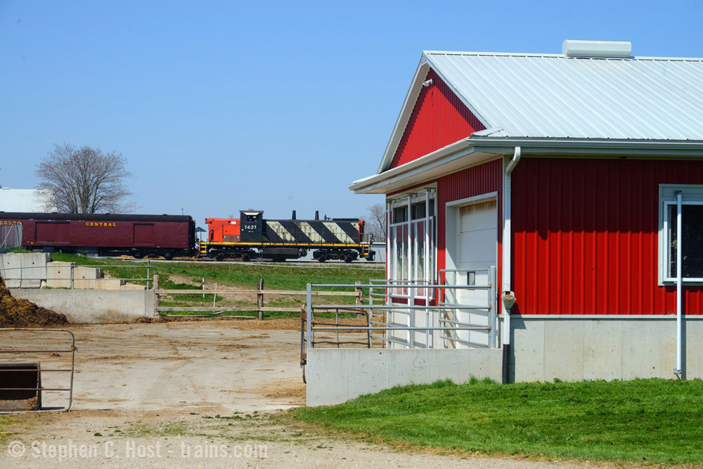 With red building in foreground, train passes in distance