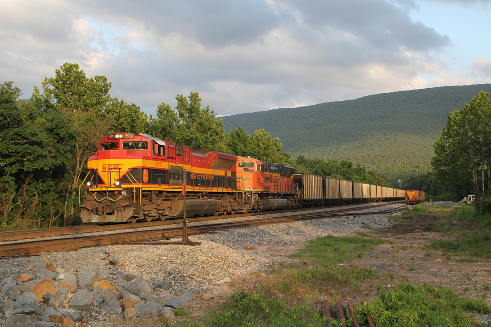KCS and BNSF engines lead coal train with mountain in distance.