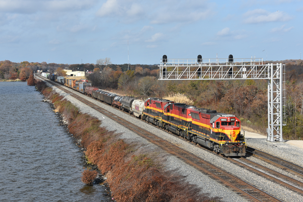 Train with three engines passes under signal bridge on track next to river.