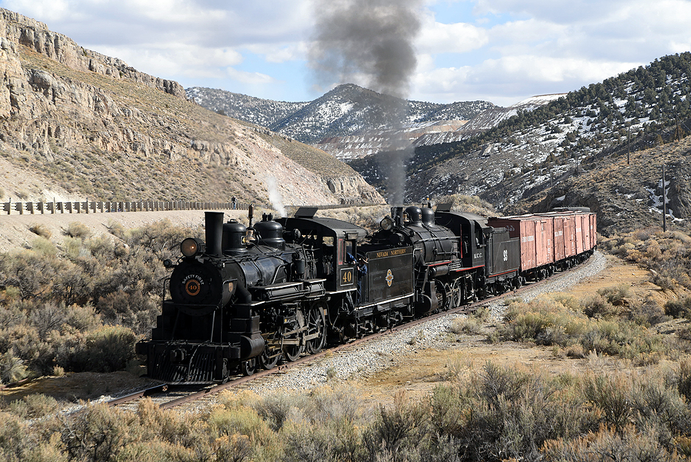 Two steam locomotive lead a freight train upgrade through a hilly valley with snow-capped mountains in the background.