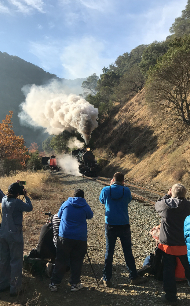 People taking pictures of steam engine
