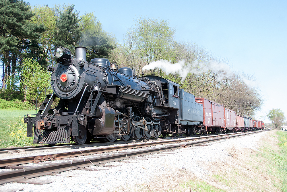 Steam locomotive hauling a freight train on a sunny day.