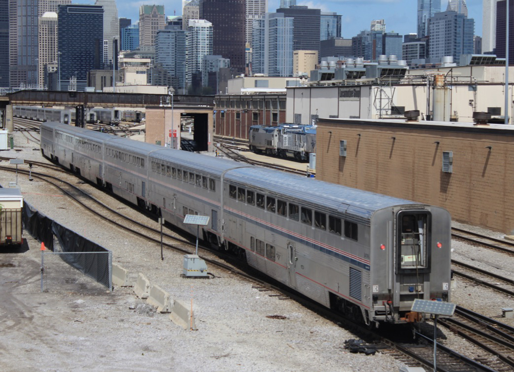 Back end of passenger train arriving in Chicago, with skyline in distance