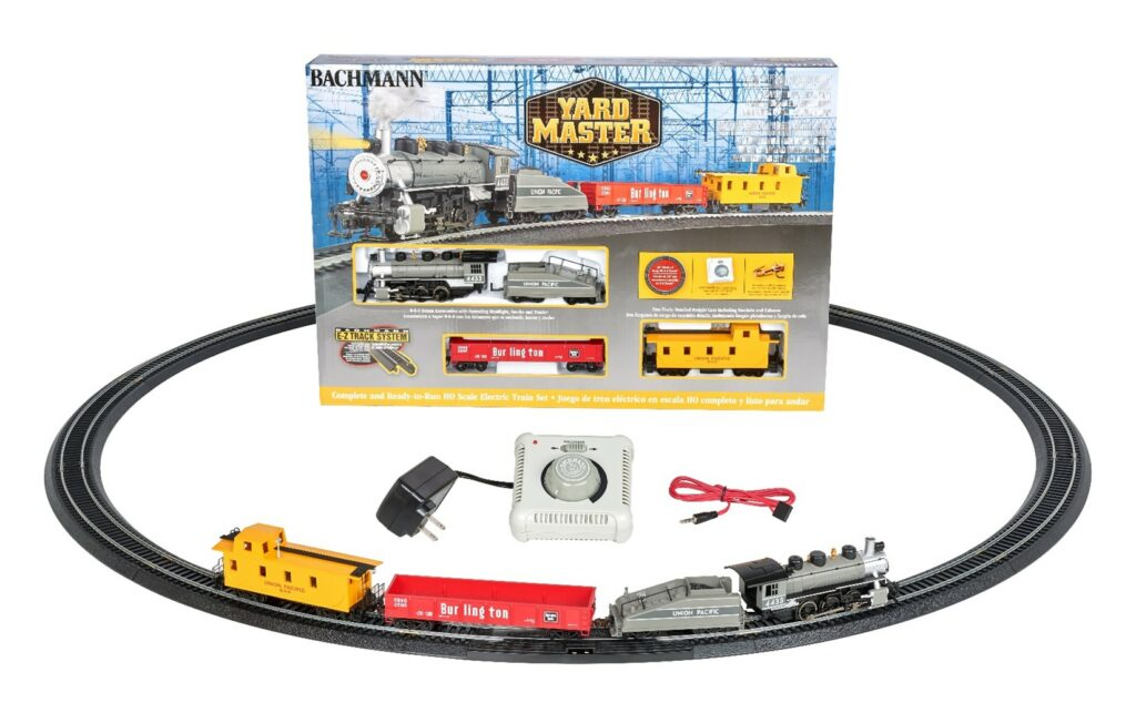 an HO scale toy train set featuring a box containing a steam locomotive, train cars, and track