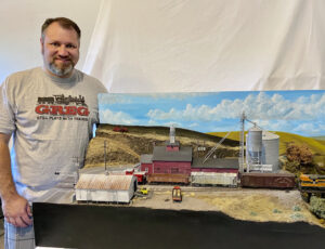 Gregory Baker, last year's adult individual winner, stands next to his layout.