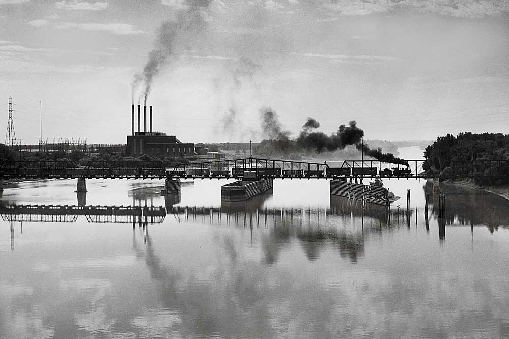 Profile of steam-powered freight train on truss bridge over wide river