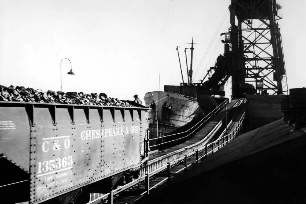 Coal hopper moves along unloading trestle alongside ship