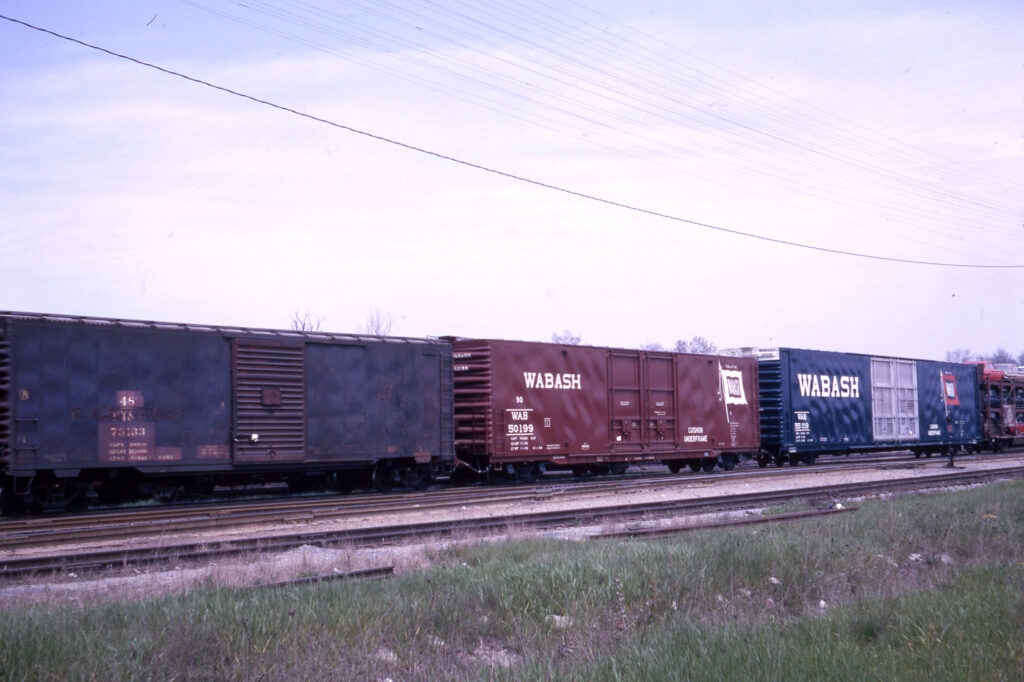 Large and small boxcars coupled together