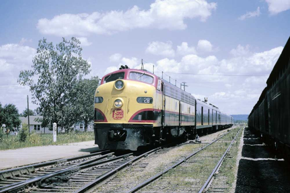 Black, red, and yellow diesel locomotive on passenger train