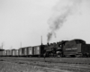 Steam locomotive switching freight cars.
