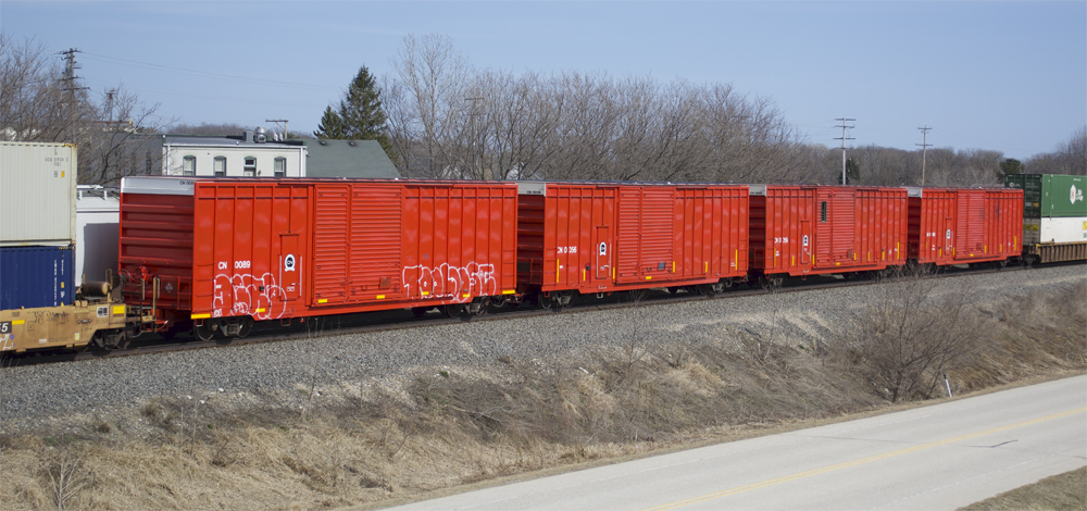 Four red CN high-cube distributed braking cars in the middle of an intermodal train.