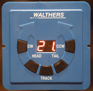 Blue Walthers controller box for turntable with five buttons arranged in a circle around an LED display showing the number 21