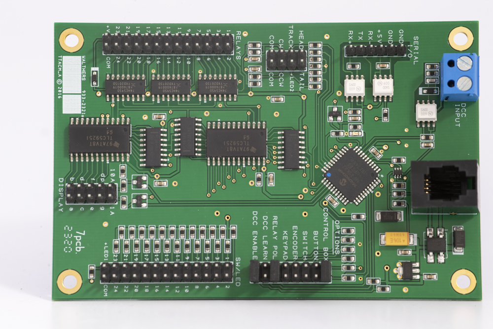Green rectangular circuit board with blue screw terminals in upper right, white plug terminals in upper left